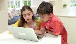 two-hispanic-children-using-laptop-at-home